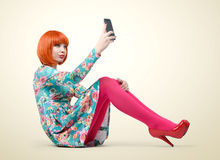 Bezauberndes junges Mädchen, das mit einem intelligenten Telefon sitzt stockbilder
