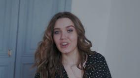 Bezauberndes junges Mädchen, das zur Kamera im modernen Innenraum aufwirft Sieherum mit Leidenschaft und Ausdruck spinnen und -b stock video footage