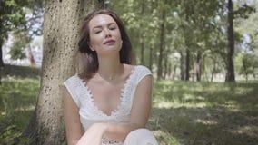 Bezauberndes junges Mädchen des Porträts mit dem langen brunette Haar, das ein langes weißes Sommermodekleid herein sitzt unter e stock footage