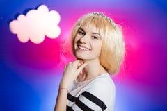 Bezauberndes lächelndes Mädchen, das blonde Perücke auf bewölktem trägt Stockbilder