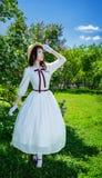 Bezauberndes Mädchen in einem weißen Kleid und in den Strohhutwegen stockbild