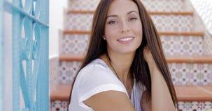 Bezauberndes Modell in der zufälligen Ausstattung, die auf gemalter Treppe aufwirft stock footage