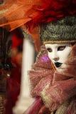 Bezauberndes Porträt mit venetianischer Maske, überraschendem farbigem Hut und schönen Augen während Venedig-Karnevals Stockbild