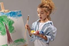 Bezauberndes Schulm?dchen malt mit einer Aquarellb?rste auf einem Gestell und steht auf einem grauen Hintergrund lizenzfreie stockbilder