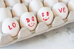 Bezauberte Eier in einem Kasten Eier mit gemalten Gesichtern Stockbilder