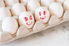 Bezauberte Eier in einem Kasten Eier mit gemalten Gesichtern Stockfotografie