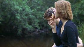 Bezauberte Jugendliche sitzen im Hintergrund der Natur und sprechen mit einander stock video