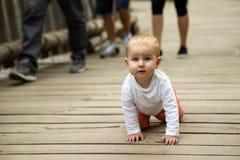 Bezbronny mały błękitnooki białogłowy dziecko czołgać się na wszystkie fo obraz stock