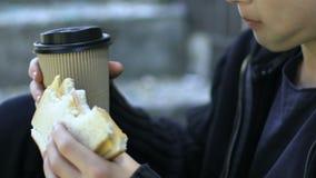 Bezdomna chłopiec łasowania kanapka i pić outdoors kawa, ubóstwo, zbliżenie zbiory wideo