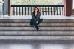 Bezdomna dziewczyna, Młoda czerwona włosiana dziewczyna siedzi samotnego outdoors na schodkach budynek z czuciowy niespokojnym, k zdjęcie stock