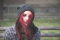 Bezdomna dziewczyna, Młoda czerwona włosiana dziewczyna siedzi samotnego outdoors z, niespokojnym i przygnębiony kapeluszowi i ko zdjęcie stock
