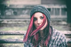 Bezdomna dziewczyna, Młoda czerwona włosiana dziewczyna siedzi samotnego outdoors z, niespokojnym i przygnębiony kapeluszowi i ko fotografia royalty free