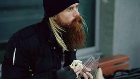Bezdomna młodego człowieka łasowania kanapka i pić przy miasto ulicą w wieczór alkohol od papierowej torby na ławce zdjęcia royalty free