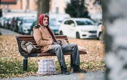 Bezdomny żebraka mężczyzna z torby obsiadaniem na ławce outdoors w mieście kosmos kopii zdjęcia royalty free