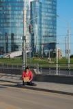 Bezdomny facet siedzi na chodniczku z kartonem i inskrypcją: potrzeba pieniądze W tle jest centrum biznesu Obraz Stock