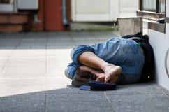 Bezdomny mężczyzna śpi na ulicie w cieniu, fotografia stock