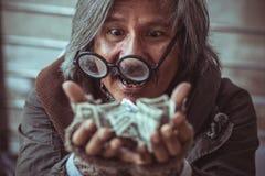 bezdomny mężczyzna dostać mnóstwo pieniądze na on ręki które robią szczęśliwej twarzy z uśmiechem fotografia royalty free