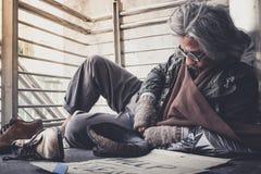 Bezdomny mężczyzna na kącie przejście ulica w mieście czekać na dobroć ludzi daje pieniądze lub jedzeniu zdjęcie stock