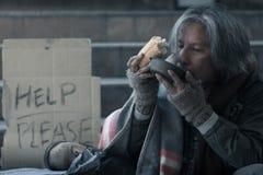 Bezdomny mężczyzna na schodku przejście ulica w miasta łasowania mleka i chleba dobroci formularzowych ludziach daje on obraz stock