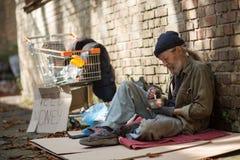 Bezdomny mężczyzna obsiadanie na kartonowym łasowaniu fotografia stock