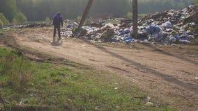 Bezdomny mężczyzna odprowadzenie wzdłuż śmieciarskiego rozsypiska w usypie Głód i ubóstwo zbiory wideo