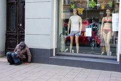 Bezdomny mężczyzna siedzi blisko okno sklep zdjęcia royalty free