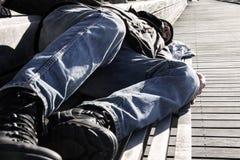 Bezdomny mężczyzny lub uchodźcy dosypianie na drewnianej ławce z butelką zdjęcia stock