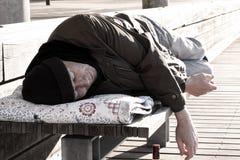 Bezdomny mężczyzny lub uchodźcy dosypianie na drewnianej ławce z butelką obraz royalty free