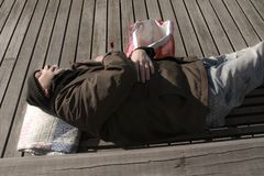 Bezdomny mężczyzny lub uchodźcy dosypianie na drewnianej ławce z butelką obraz stock