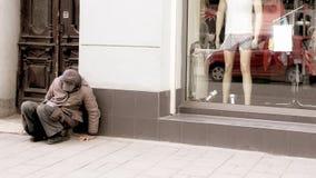 Bezdomny m??czyzna siedzi blisko okno sklep obraz stock