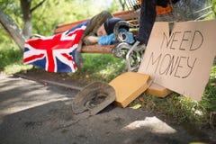 Bezdomny starego człowieka dosypianie na ławce, błaga dla pieniądze obrazy stock