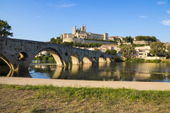 Beziers, France. Views at sunset of the French city of Beziers, with trees and the old bridge reflected over the river Orb, and the 13th-century Cathedral of Royalty Free Stock Image