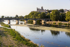Beziers, France. Views at sunset of the French city of Beziers, with trees and one of its bridges reflected over the river Orb, and the 13th-century Cathedral of Stock Photos