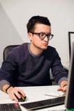 Bezig het werken Peinzende jonge knappe mens die glazen op laptop dragen terwijl het zitten op zijn het werkplaats stock afbeeldingen