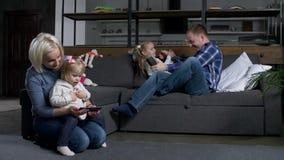 Bezig met het rustende huis van de smartphonesfamilie stock footage