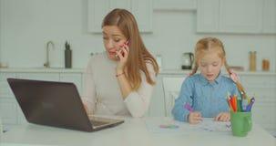Bezig mum het werk overwerk terwijl kindtekening stock videobeelden