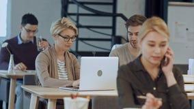 Bezig ontwerpbureau met arbeiders bij bureaus stock foto