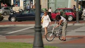 Bezig straatverkeer, het actieve stedelijke leven die, vrouw weg, dame het bevestigen fiets kruisen stock video