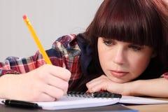 Bezig studentenmeisje het schrijven thuiswerk met potlood Stock Afbeelding