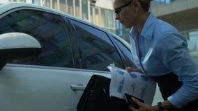 Bezig wijfje die haastig van auto weggaan, houdend documenten, die zich aan bureau haasten stock video