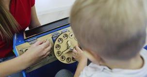 Bezige Auto Moeder met een kleine kindspelen met een houten autostuk speelgoed stock footage