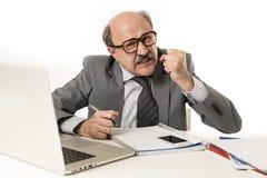 Bezige bedrijfsmens met kaal hoofd bij zijn jaren '60 werken boos en gefrustreerd bij laptop van de bureaucomputer bureau die ver Stock Foto's