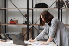 Bezige bedrijfsvrouw die zich dichtbij lijst in bureau bevinden stock afbeelding