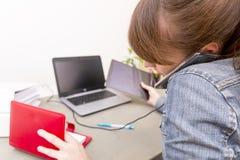 Bezige beklemtoonde vrouw die op een celtelefoon spreken terwijl het gebruiken van laptop a stock foto