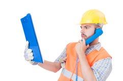Bezige bouwer die telefoon op witte exemplaarruimte met behulp van Stock Fotografie