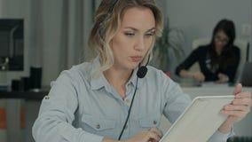 Bezige call centreagent die digitale tablet op een vraag gebruiken op het haar werk stock fotografie