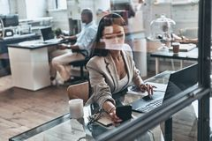 Bezige dag Hoogste mening van moderne jonge vrouw die computer met behulp van terwijl wo stock foto