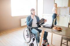 Bezige jonge student op rolstoel die en telefoon bestuderen overnemen Kerel met speciale behoeften en onbekwaamheid Geopende hold stock foto