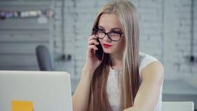Bezige jonge vrouwenzitting in bureau en het spreken op cellulair stock footage