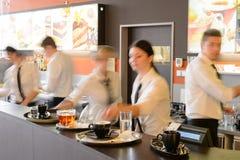 Bezige kelner en serveersters die bij bar werken Stock Foto's